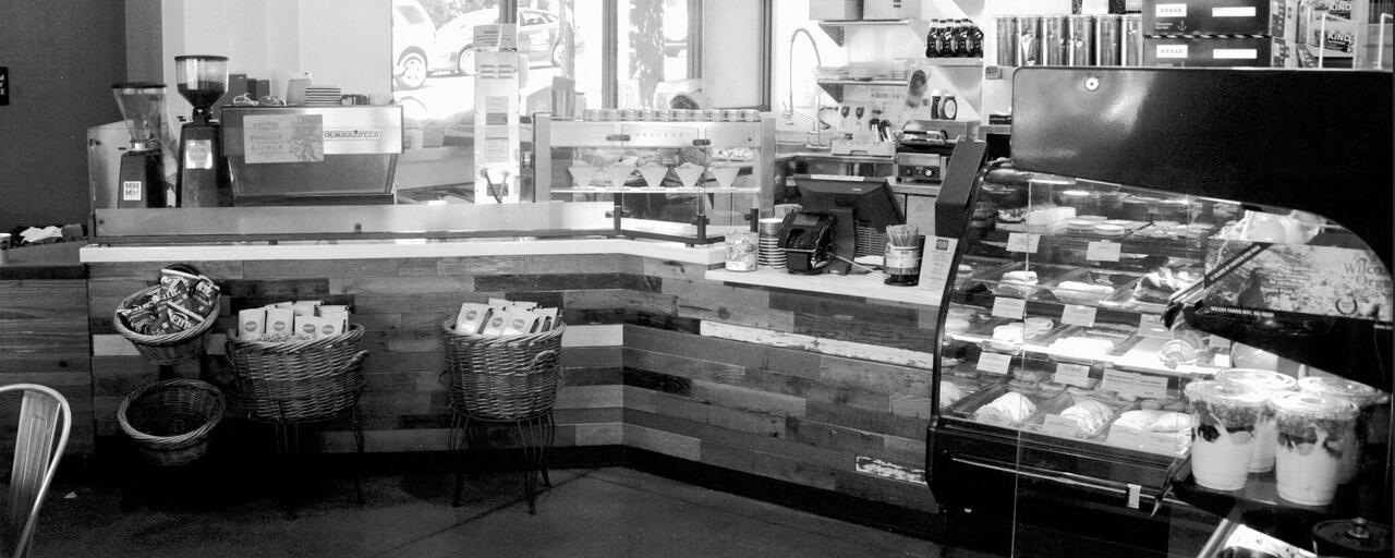 Wood-paneled counter of coffee and beer bar with espresso machines, baskets of coffee products, register and bakery display cases.