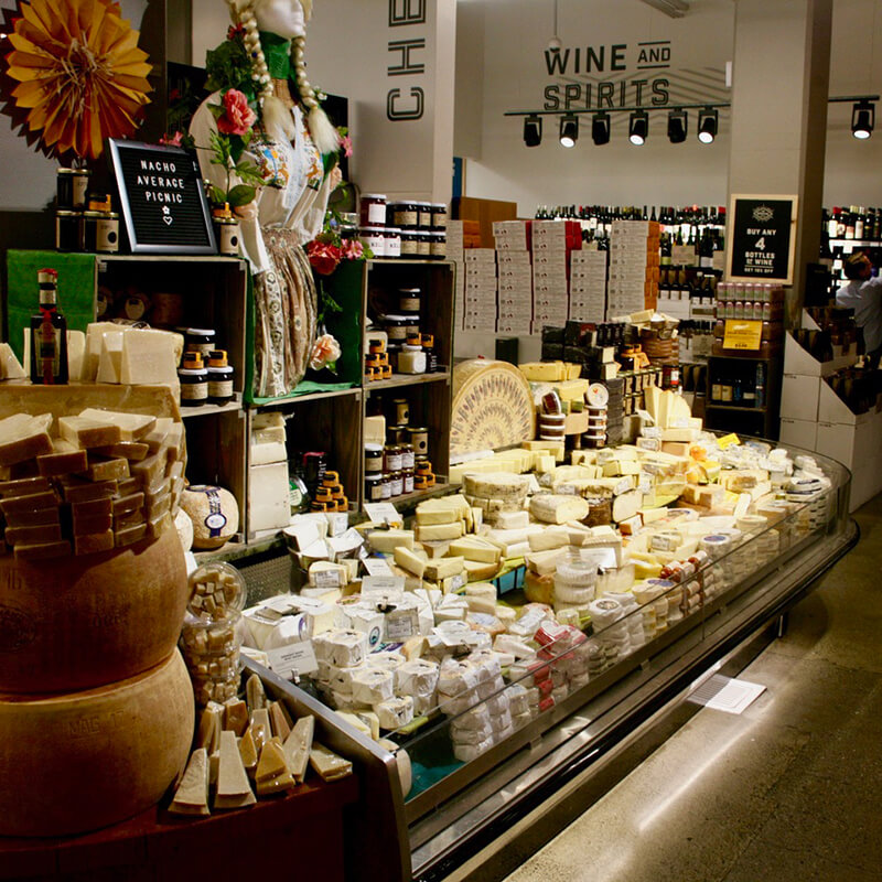 An enticing display of cheeses and fruit preserves at a grocery store.