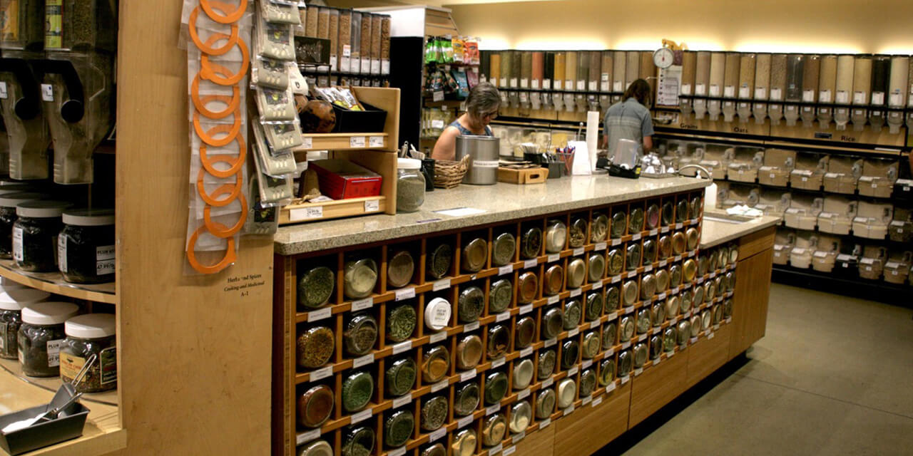 Bulk spices, grains and other food items stored in glass containers in cubbyholes and rows of wall dispensers, creating a patchwork earthtone design.