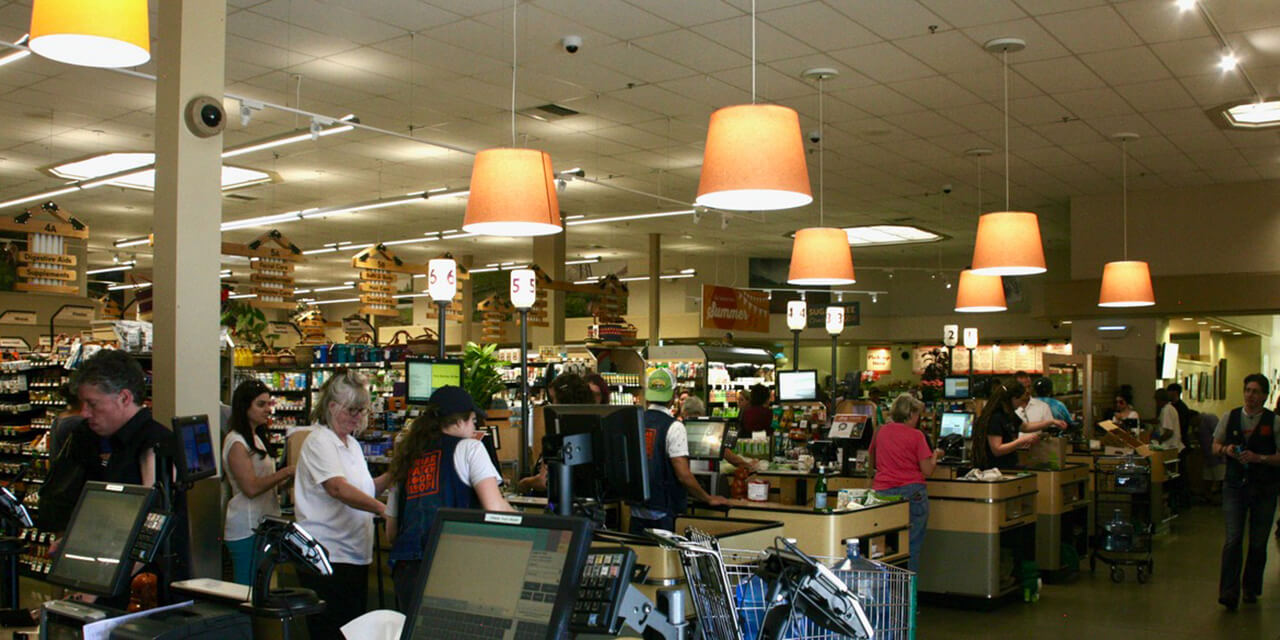 Over a dozen grocery store customers and clerks interact at six checkout areas.
