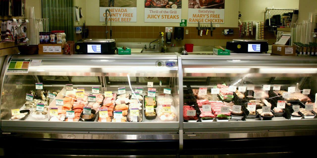 Fresh meats aligned in refrigerated case. Large wall signs highlight 'Nevada County Free Range Beef' and other options.