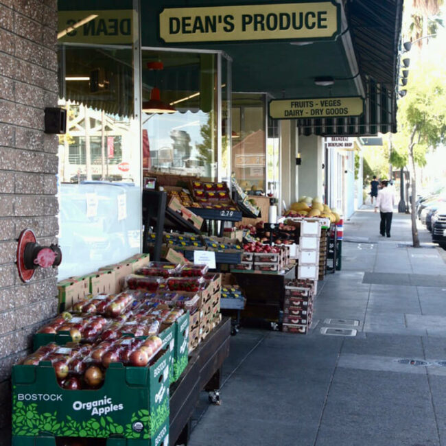 "To the left of a sidewalk, a sign reading ""Dean's Produce"" hang above boxes of organic apples and other fruit by the front entrance of a grocery."