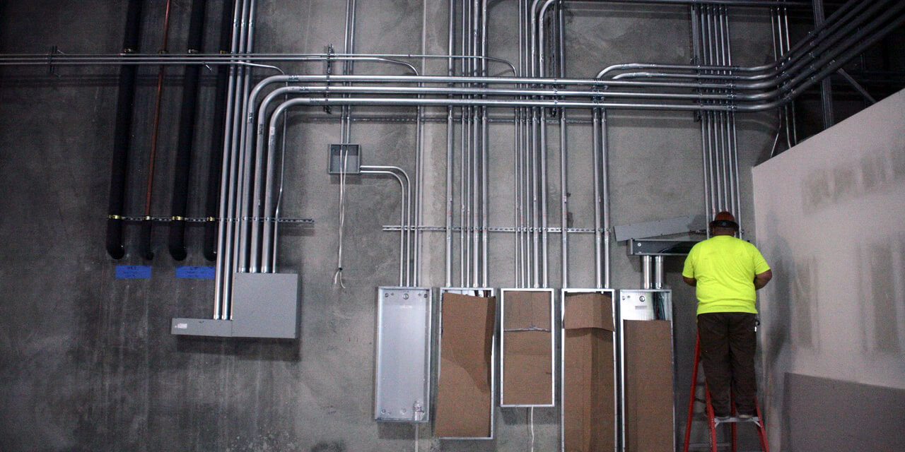 Construction professional works on metal pipes that extend from control boxes to form a pattern of parallel and perpendicular lines.