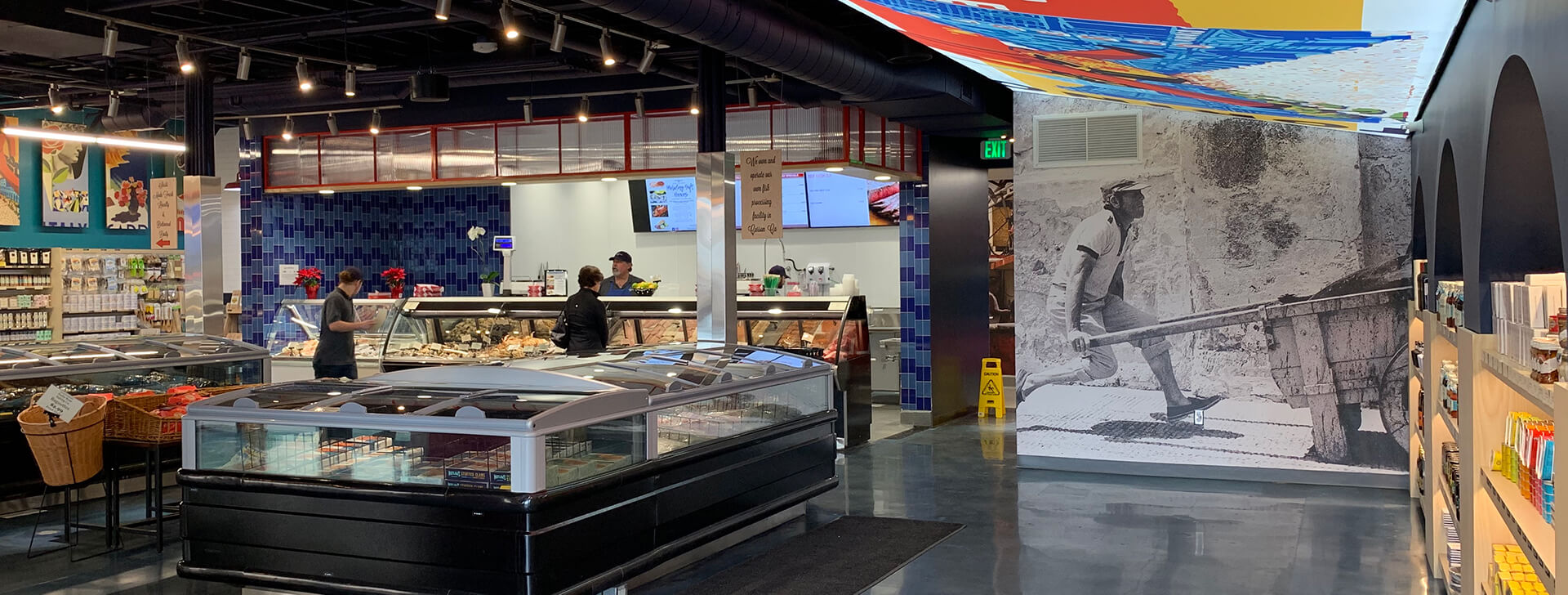 Seafood market interior with seafood cooler cases and bold interior design featuring large vibrant lighted signs, black and white photography, brightly painted walls, woven baskets and dramatic two-tone blue tiles.