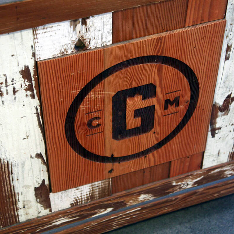 Closeup of wooden box made of old barn boards with graphic branded into wood: a black circle with large letter 'G' surrounded by small 'c' and 'm'.
