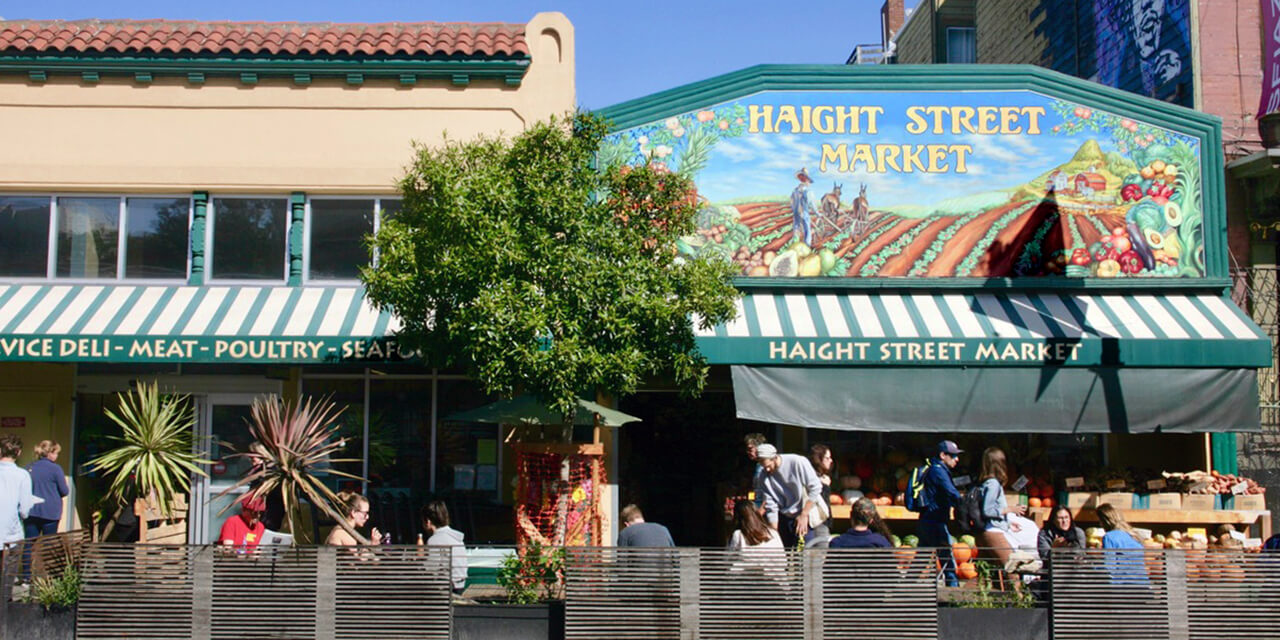 On a sunny day, groups of people relax at outdoor tables — talking and eating outside the Haight Street Market.