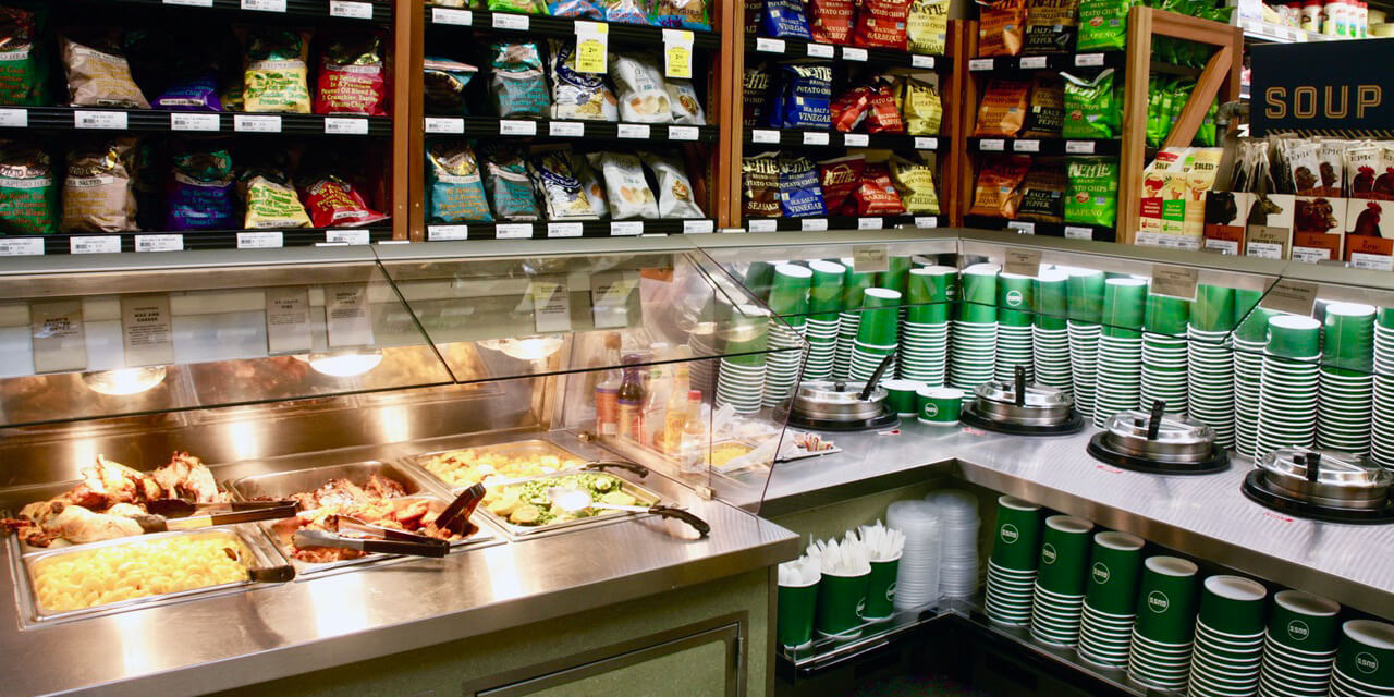 Stainless steel counters below glass guards are tucked in a store corner, enticing customers with appetising, hot foods, including four soup tureens.