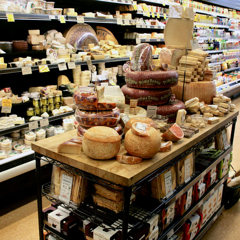 Rounds and blocks of cheeses are piled high on a butcher-block table, with speciality crackers on the shelves below. Behind the table, refrigerated cases a filled with more cheese along with fresh juices.