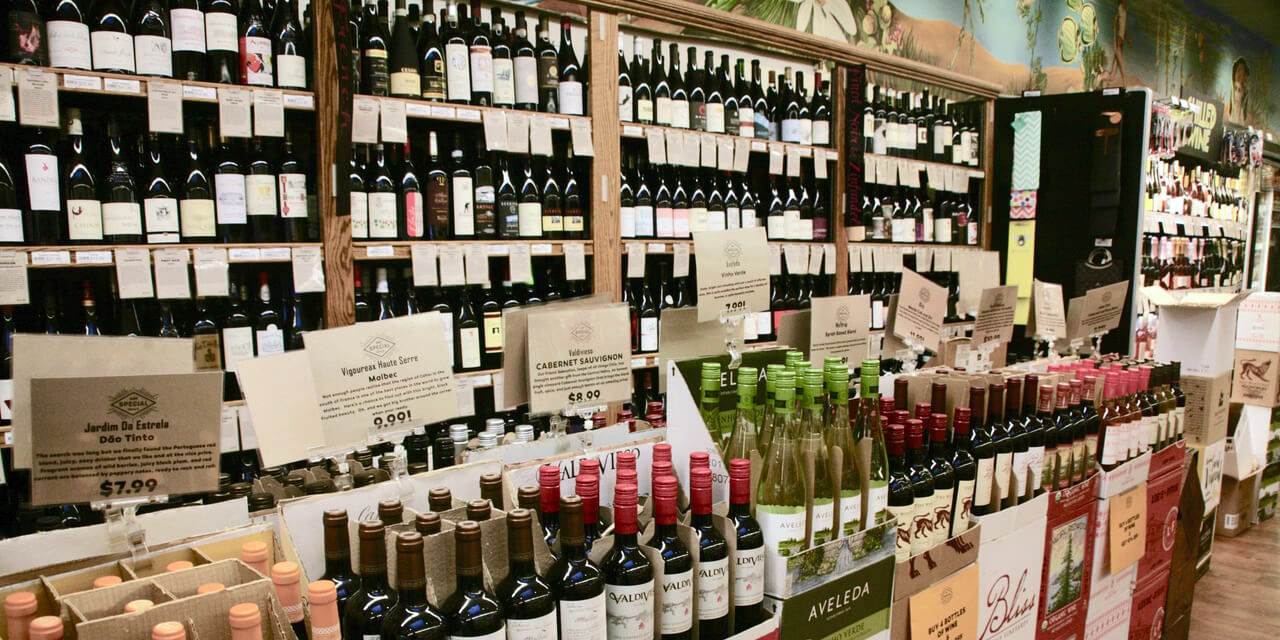A mural in soft blues and greens decorates the wall above wooden shelves and refrigerated cases filled with a huge selection of wines.