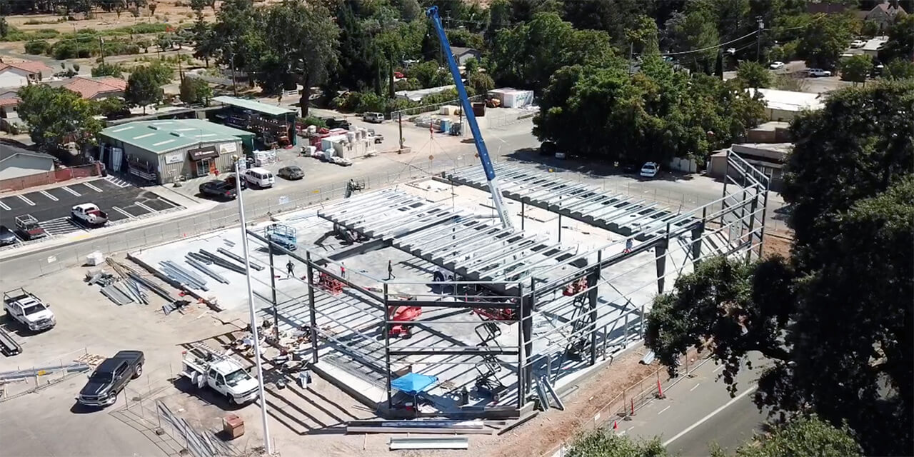 Aerial view of two-story space under construction with a crane lowering beams into place.