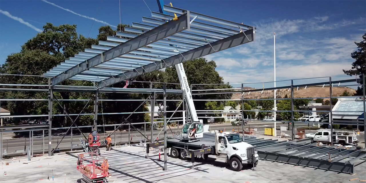 Massive metal structure of support beams and cross beams is moved into place by a crane and construction workers.