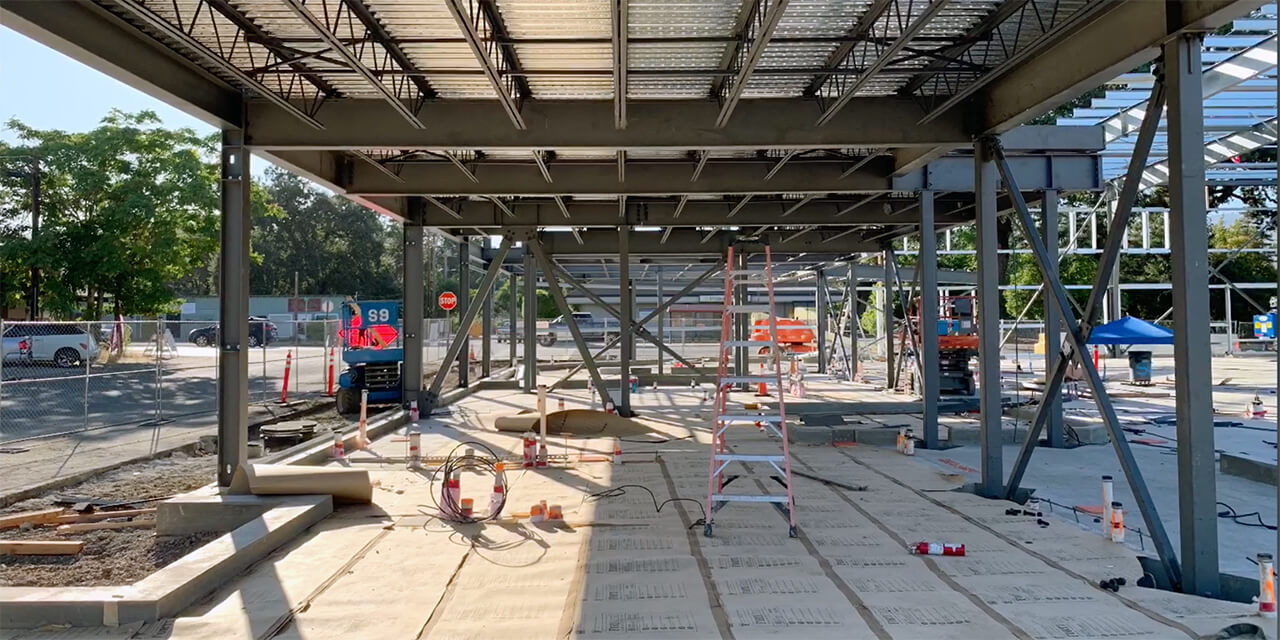 Construction site. Steel girders and beams form first floor of building under construction.
