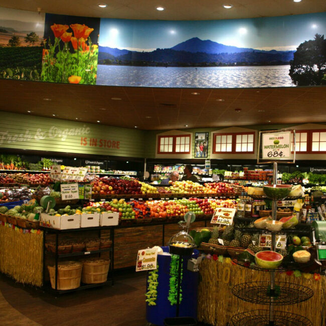 Fruit and vegetables in produce section of a grocery store are surrounded set off by huge full-color photos of flowers and landscapes.