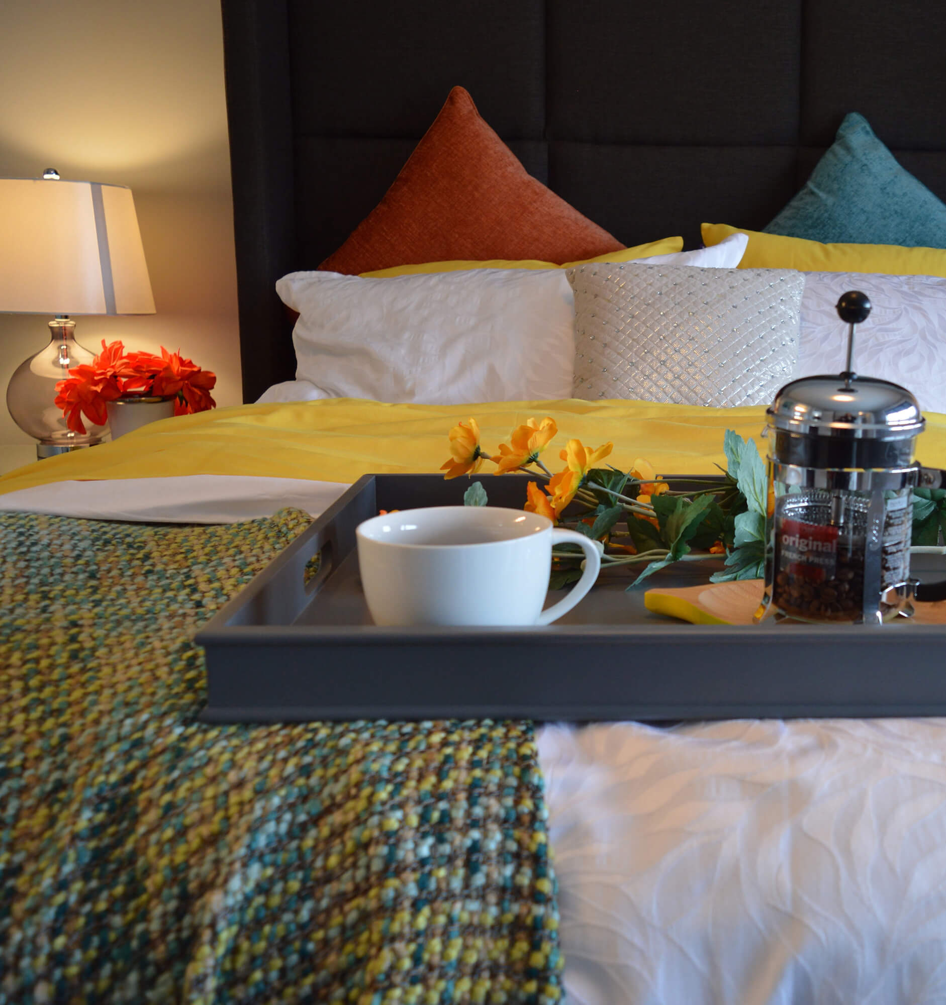 Food tray with coffe cup and carafe on end of bed in hotel guestroom decorated with colorful pillows, throw blanket, and flowers.